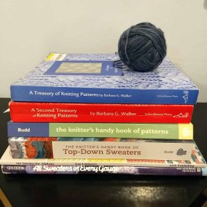 pile of knitting/crochet books with ball of yarn on top