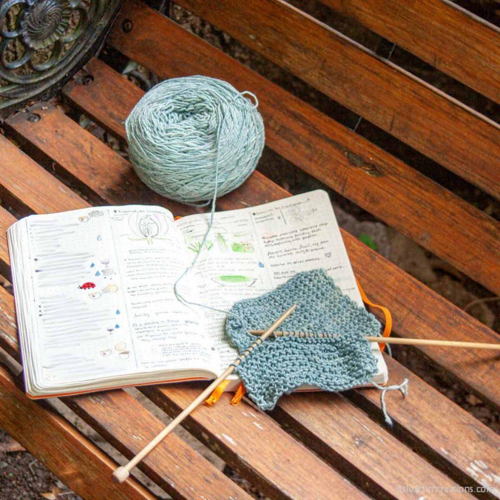 Anzula Vera garter stitch swatch in progress sitting on wooden bench and open notebook