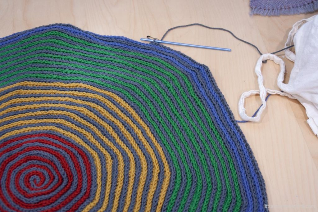 Swirly Blanket progress approximately 1/4 of the blanket circle shown laid out on wooden desk.