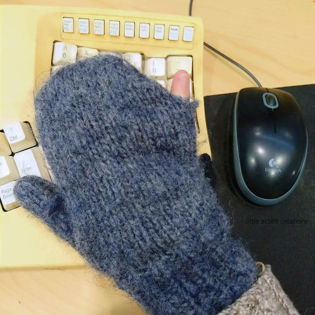 Grey hand knit mitten worn on right hand with pinkie finger poking out the side.