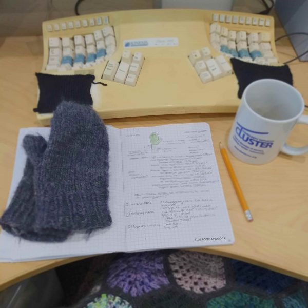 Notebook of initial sketch and notes with mittens that need mending laying on the opposite page. Also visible is a pencil, empty coffee mug, and a computer keyboard.