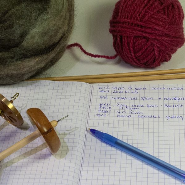 a ball of fiber, a ball of yarn, knitting needles, two spindles on top of open notebook