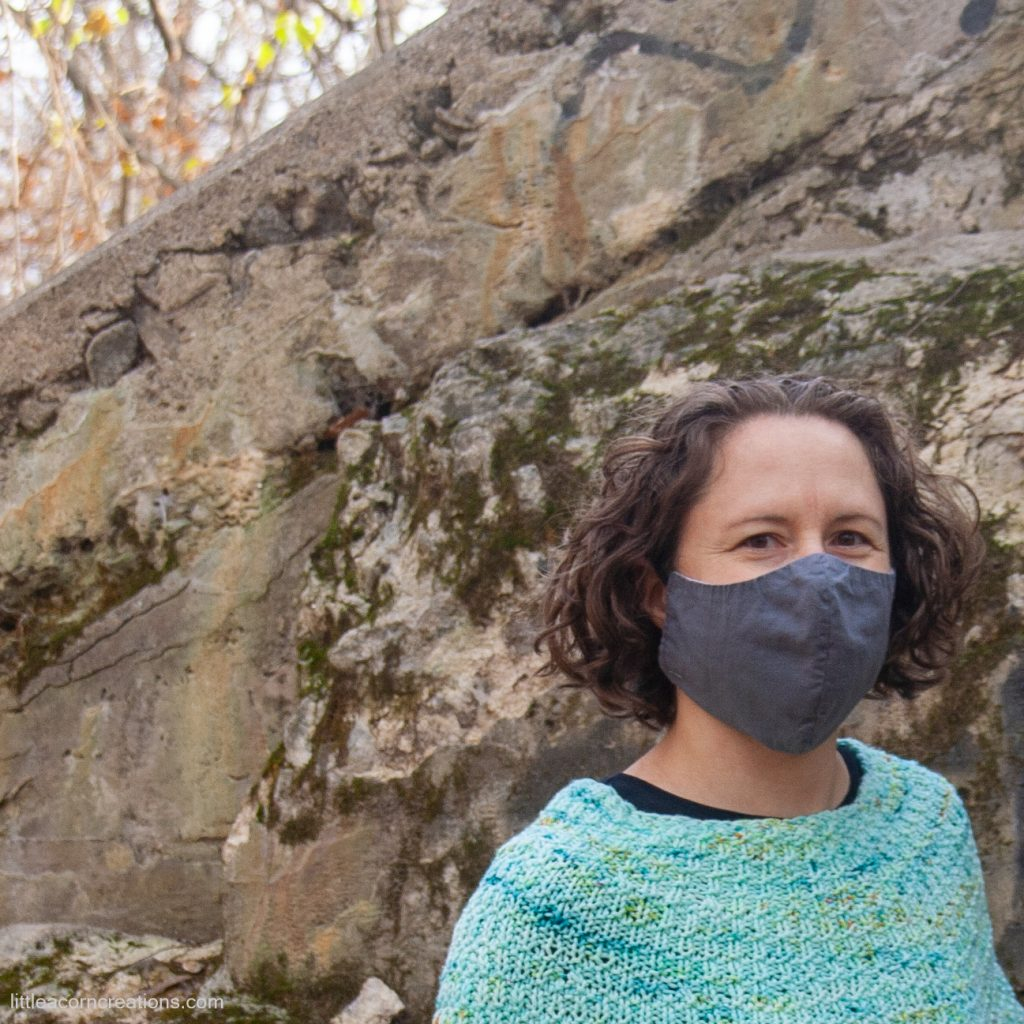 Person wearing a mask & a handknit poncho, about 3 inches of yoke is seen (photo is cropped). They are standing in front of a concrete embankment that is covered in moss and graffiti.
