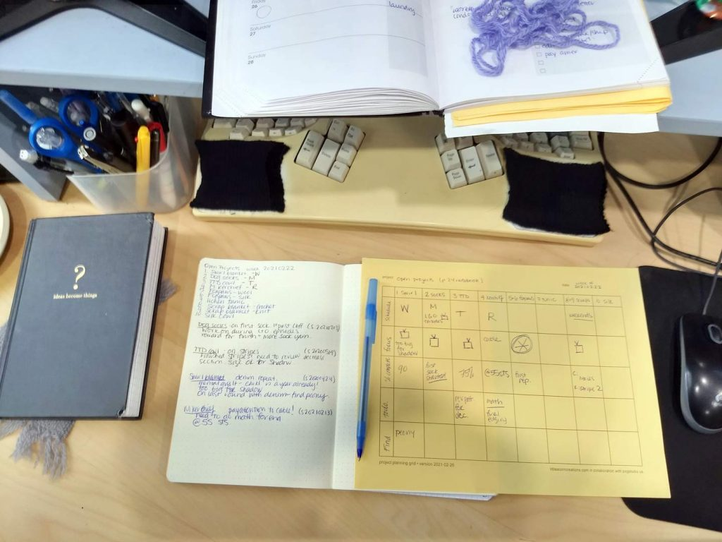 messy desk with several notebooks: attention is on the open dot grid notebook that shows open projects and the planning grid.