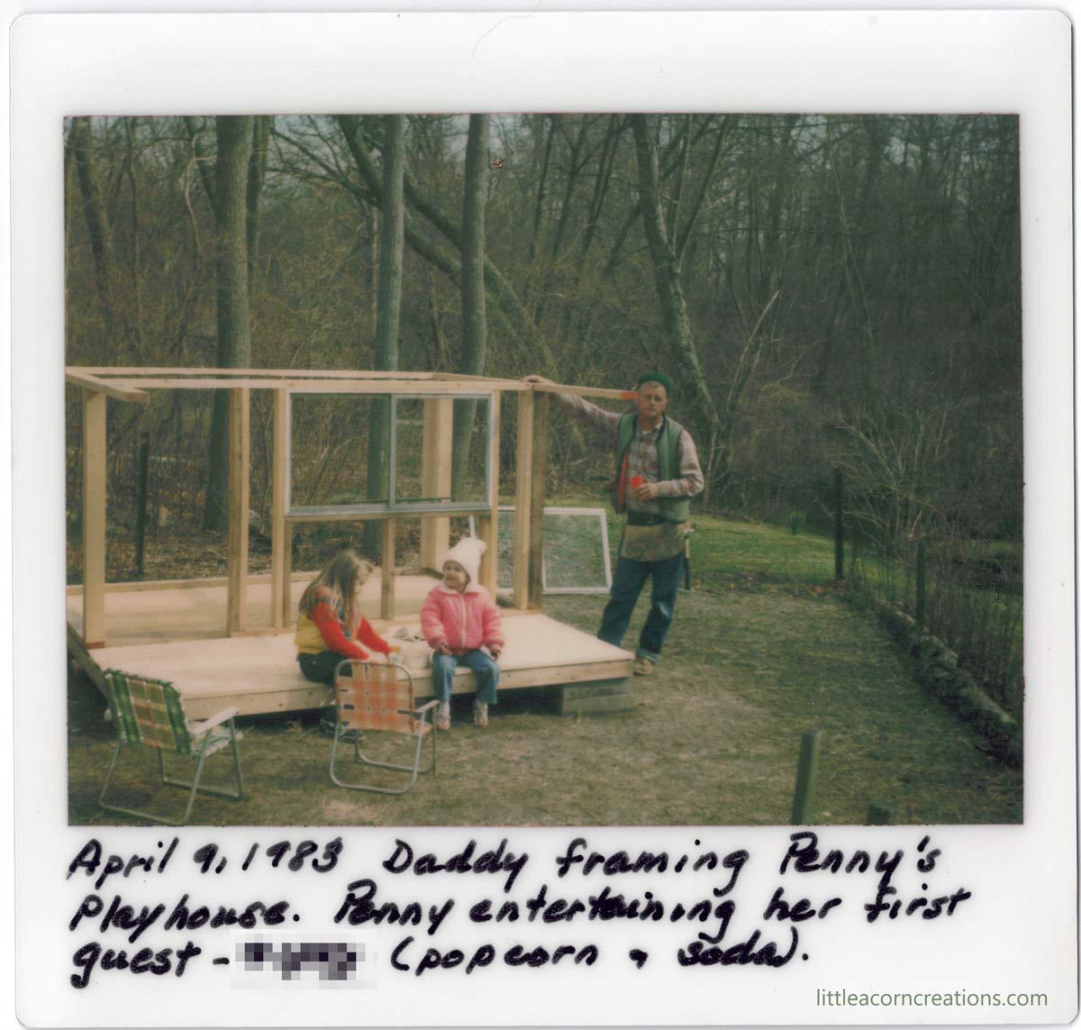 "A man in his mid 40s stands with his hands on the frame of a small wooden structure. There is a window leaning against a tree in the background. Two young children sit on the completed plywood decking sharing a snack. The polaroid image is captioned ""April 9, 1983 Daddy framing Penny's Playhouse. Penny entertaining her first guest - [name blurred] (popcorn & soda)."