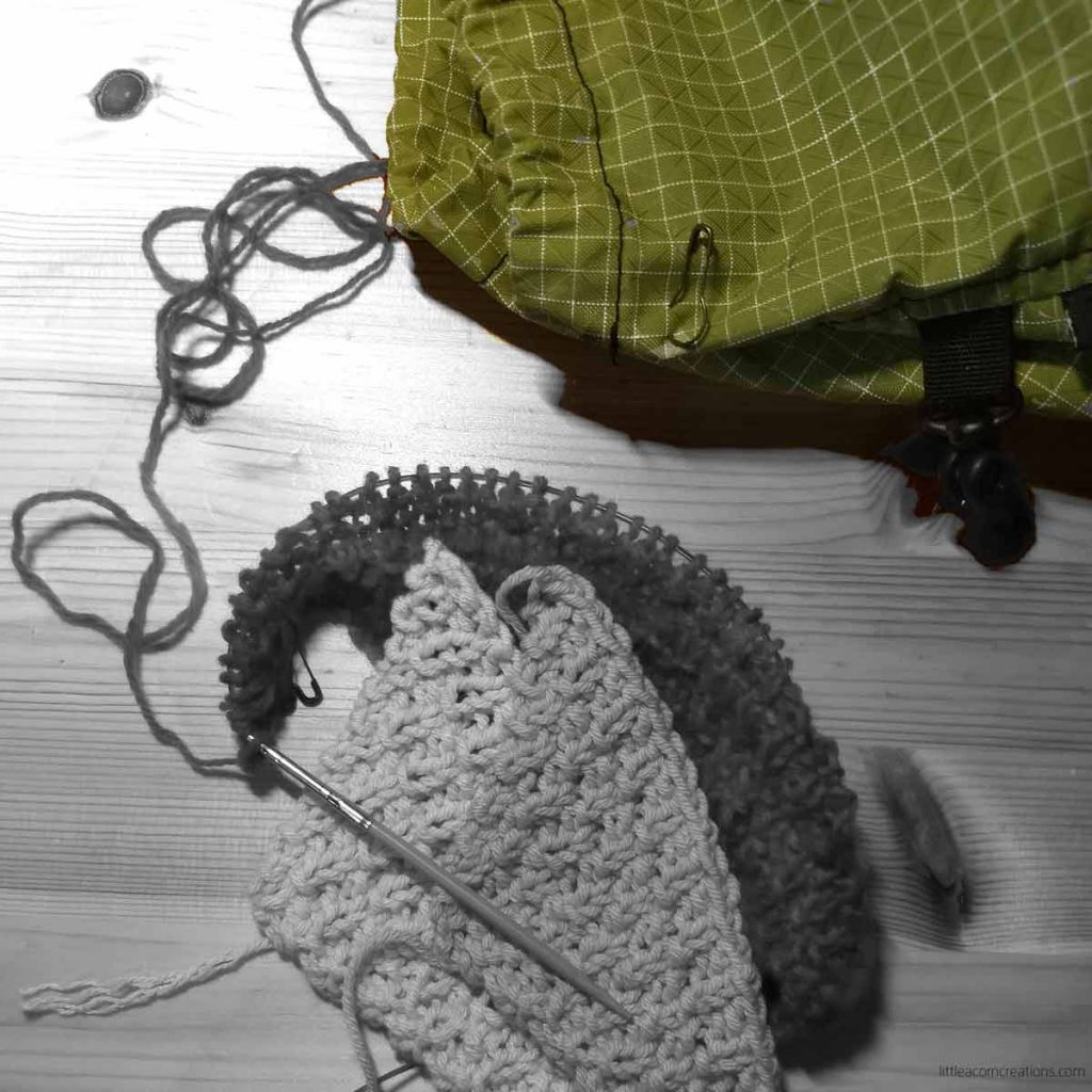 two completed swatches and another in progress shown on a wooden surface. Most of the image is in black and white with the exception of the project bag which is a wasabi green.