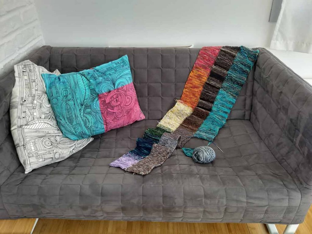 a knit blanket in progress laying on a small dark blue couch